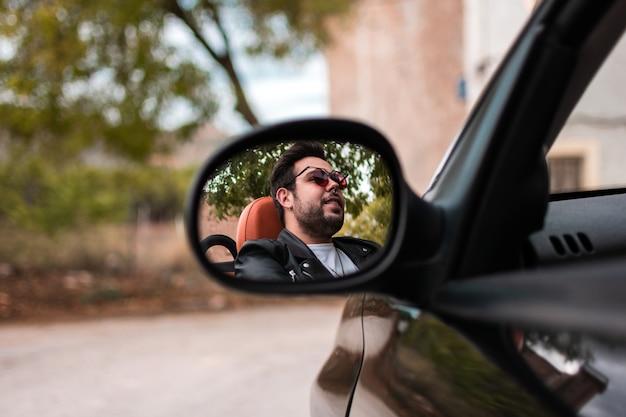 Jovem dirigindo carro conversível.
