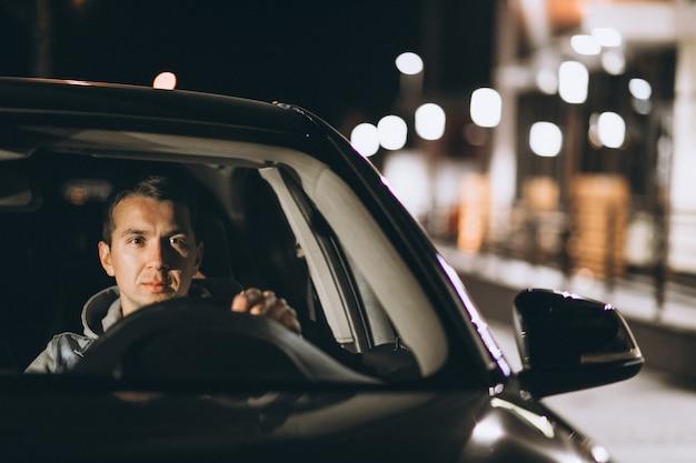 Jovem dirigindo seu carro durante a noite