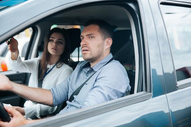Jovem dirigindo um carro com seu instrutor