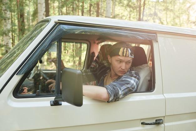 Jovem dirigindo um ônibus ao longo da floresta com pessoas ao fundo