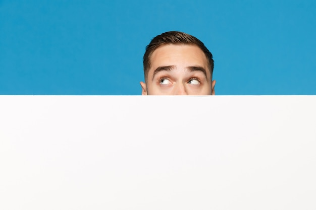 Jovem divertido se escondendo, olhe os olhos grande outdoor em branco vazio para conteúdo promocional isolado no retrato de estúdio de fundo de parede azul. conceito de estilo de vida de emoções de pessoas. simule o espaço da cópia.