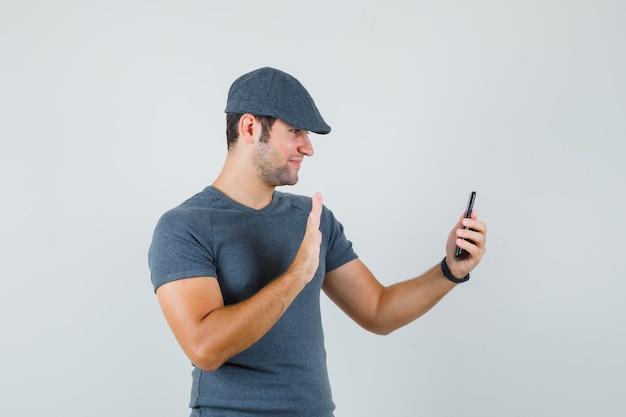 Jovem do sexo masculino acenando com a mão no chat de vídeo usando um boné de camiseta e parecendo alegre