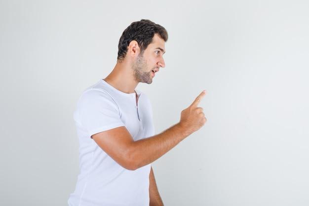 Jovem do sexo masculino alertando alguém com um gesto em uma camiseta branca e parecendo zangado