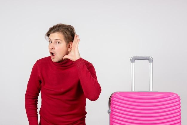 Jovem do sexo masculino com bolsa rosa em fundo branco