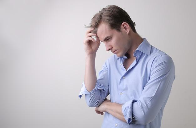 Jovem do sexo masculino com camisa azul e pensamentos profundos em pé contra uma parede branca Foto gratuita