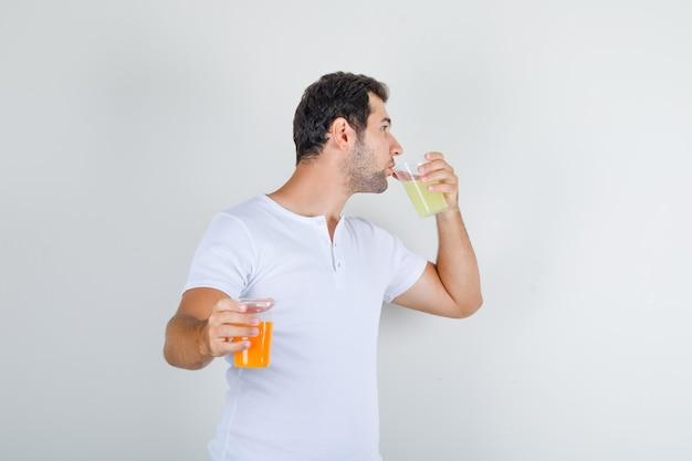 Jovem do sexo masculino com camiseta branca bebendo um copo de suco e parecendo com sede