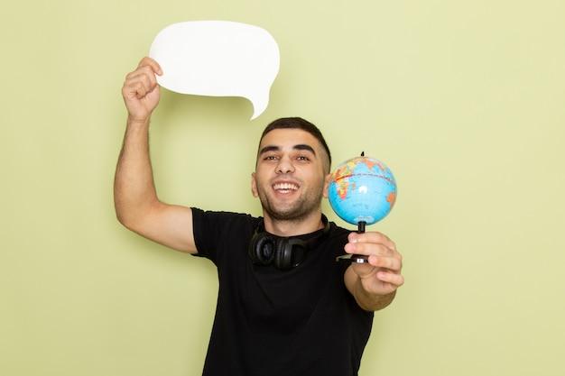Jovem do sexo masculino com camiseta preta segurando uma placa branca e um globo verde