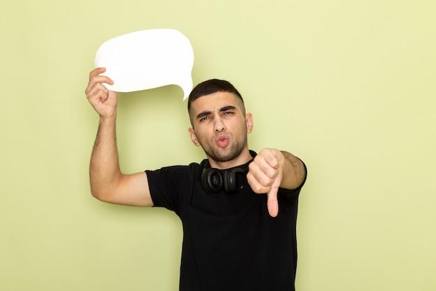 Jovem do sexo masculino com camiseta preta segurando uma placa branca mostrando o contrário no verde