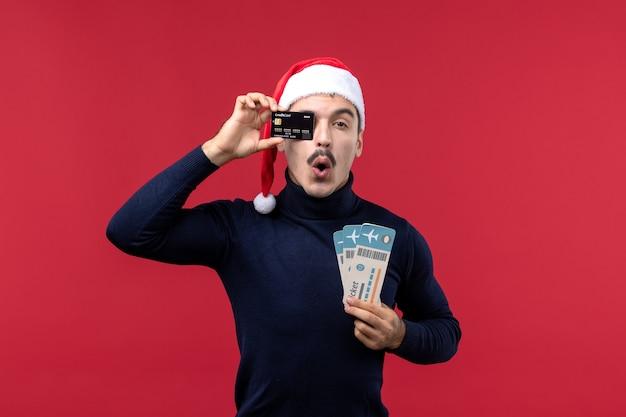 Jovem do sexo masculino com cartão de banco e ingressos em fundo vermelho.