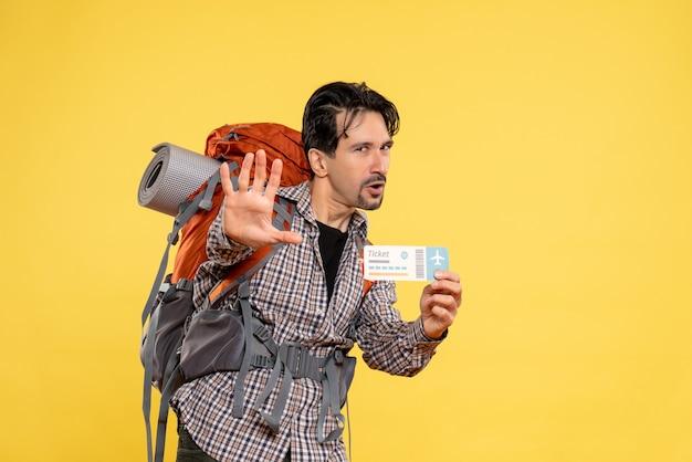 Jovem do sexo masculino com mochila segurando bilhete amarelo