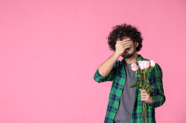 Jovem do sexo masculino com rosas cor de rosa na frente