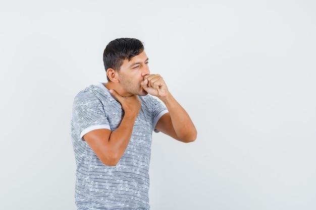 Jovem do sexo masculino com tosse usando uma camiseta e parecendo doente