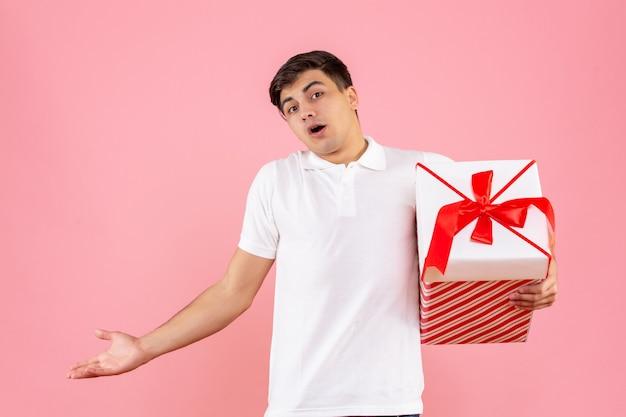 Jovem do sexo masculino com um grande presente de natal no fundo rosa