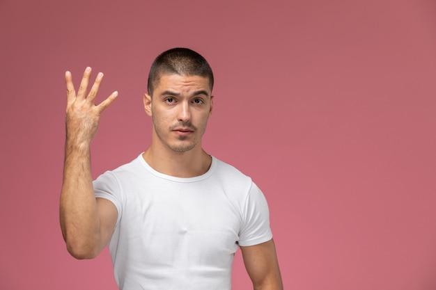 Jovem do sexo masculino com uma camiseta branca posando de frente para o outro, mostrando quatro sinais no fundo rosa