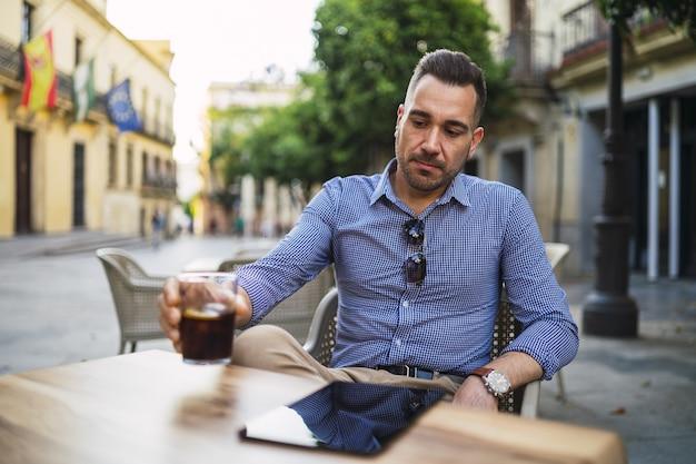 Jovem do sexo masculino com uma roupa formal sentado em um café ao ar livre bebendo uma bebida gelada