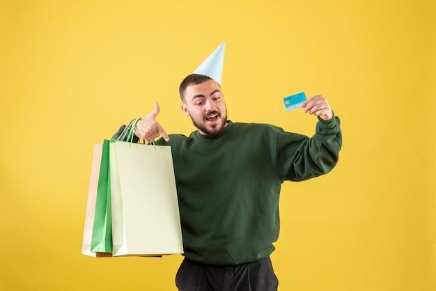 Jovem do sexo masculino com vista frontal, segurando o cartão do banco e pacotes de compras em fundo amarelo