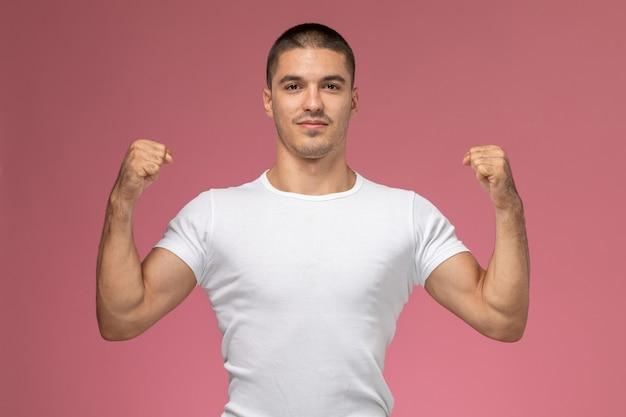 Jovem do sexo masculino de camisa branca torcendo de frente com os braços erguidos sobre fundo rosa