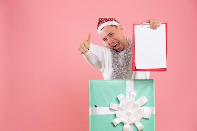 Jovem do sexo masculino de frente para dentro do presente segurando notas de arquivo no fundo rosa