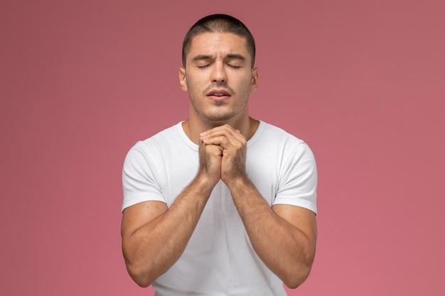 Jovem do sexo masculino de frente para uma camiseta branca em oração, posando em fundo rosa