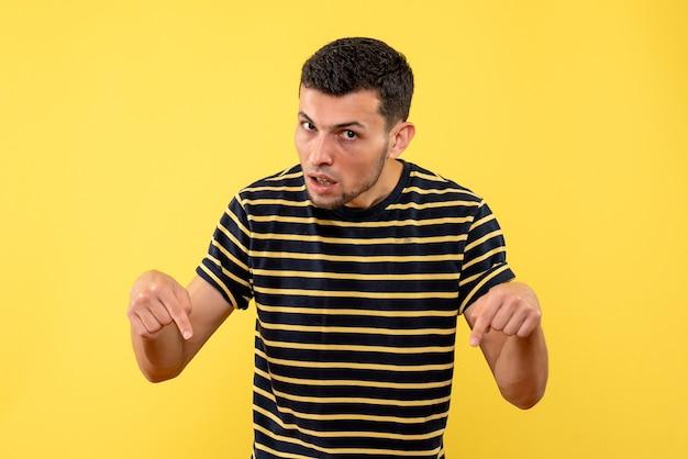 Jovem do sexo masculino de vista frontal com camiseta listrada em preto e branco apontando para o chão amarelo isolado.