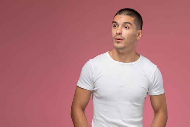 Jovem do sexo masculino de vista frontal em uma camiseta branca, simplesmente posando no fundo rosa