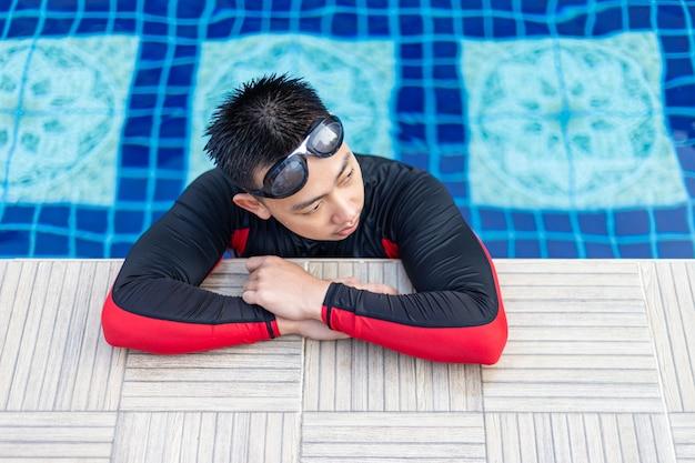 Jovem do sexo masculino descansando sua natação com prática, segurando a piscina.