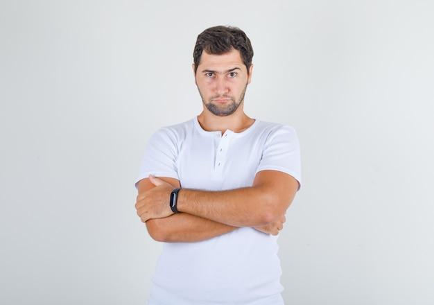 Jovem do sexo masculino em pé com os braços cruzados em uma camiseta branca e parecendo pensativo