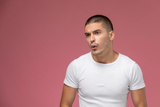 Jovem do sexo masculino em uma camiseta branca com expressão de surpresa no fundo rosa