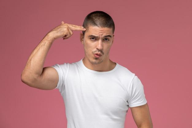 Jovem do sexo masculino em uma camiseta branca, de frente para a frente, posando tocando sua têmpora no fundo rosa
