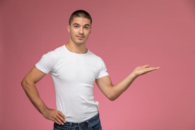 Jovem do sexo masculino em uma camiseta branca posando com a palma da mão levantada em um fundo rosa