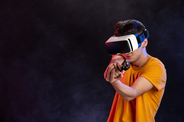 Jovem do sexo masculino jogando realidade virtual com uma arma em um vídeo de tecnologia de videogame escuro