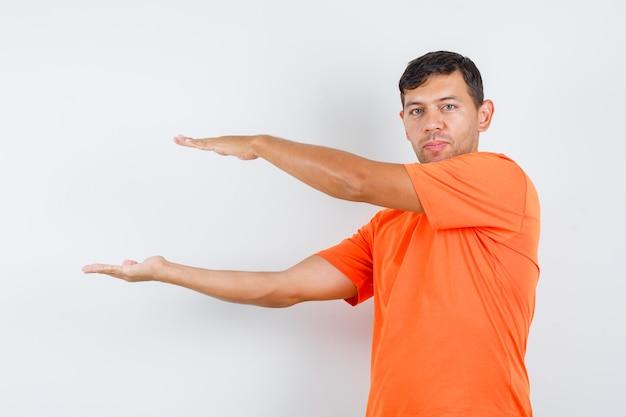 Jovem do sexo masculino mostrando sinal de tamanho em camiseta laranja e parecendo sensato