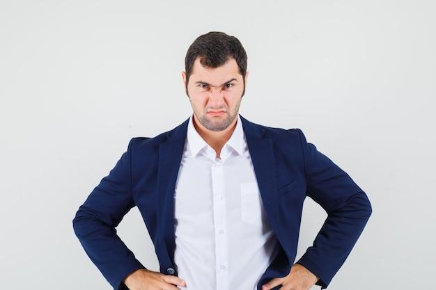 Jovem do sexo masculino segurando as mãos na cintura com camisa e jaqueta e parecendo triste
