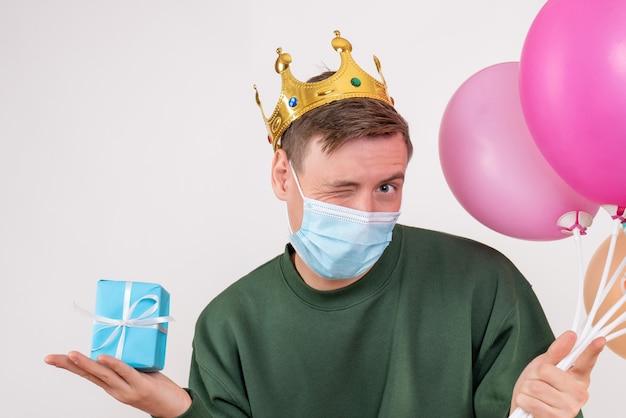 Jovem do sexo masculino segurando balões coloridos e um presentinho em branco
