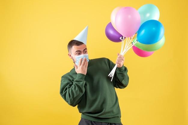 Jovem do sexo masculino segurando balões coloridos em um amarelo