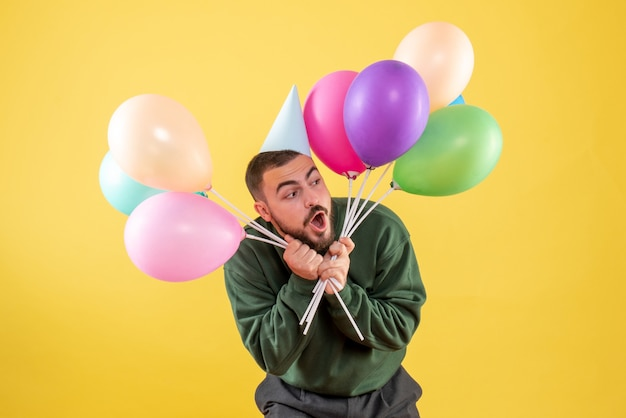 Jovem do sexo masculino segurando balões coloridos em um fundo amarelo de frente