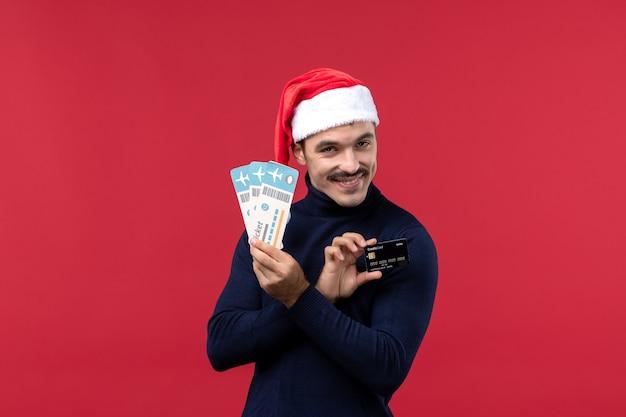 Jovem do sexo masculino segurando bilhetes de cartão do banco sobre fundo vermelho.