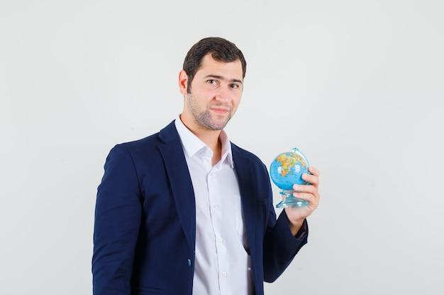 Jovem do sexo masculino segurando o globo da escola com camisa e jaqueta e parecendo confiante