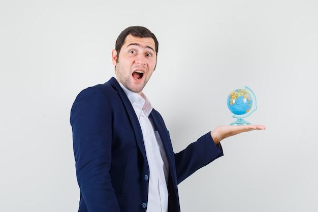 Jovem do sexo masculino segurando o globo da escola com camisa e jaqueta e parecendo surpreso