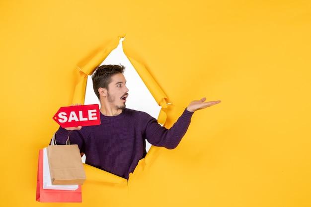 Jovem do sexo masculino segurando pequenos pacotes e escrevendo sobre a venda no fundo amarelo, cor do presente presente, compras, fotos do feriado de natal, vista frontal