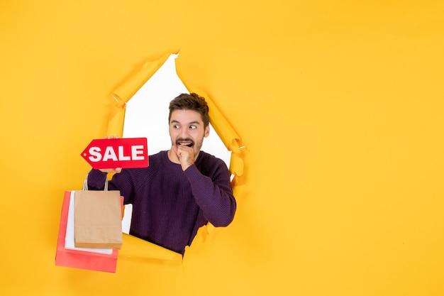 Jovem do sexo masculino segurando pequenos pacotes e escrita de venda na cor de fundo amarelo, presente de compras de ano novo, natal