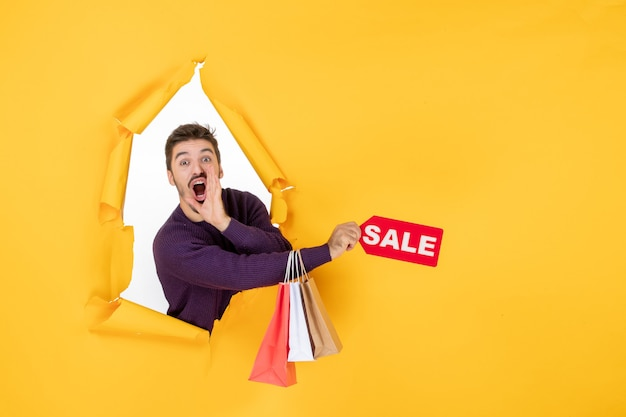 Jovem do sexo masculino segurando pequenos pacotes e escrita de venda na cor do fundo amarelo foto do dinheiro foto do dinheiro presentes de natal
