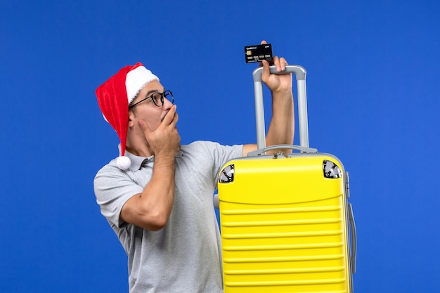 Jovem do sexo masculino segurando um cartão de banco amarelo em um fundo azul viagem férias emoções