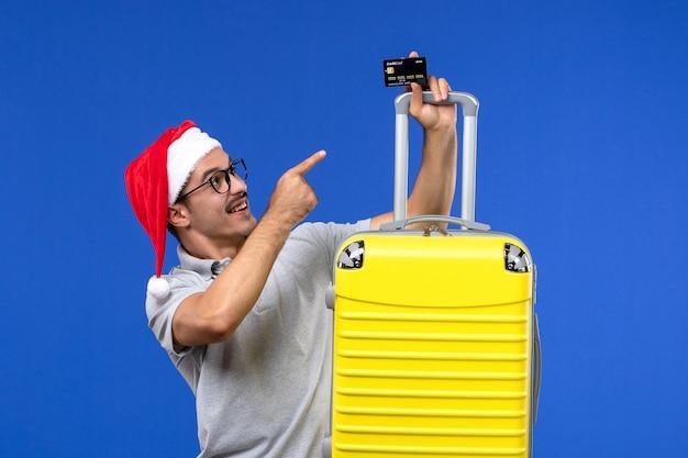 Jovem do sexo masculino segurando um cartão de banco amarelo em uma emoção de férias viagem de mesa azul de frente