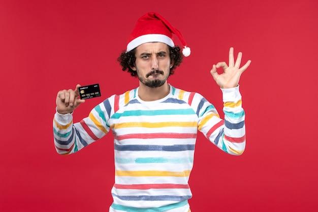 Jovem do sexo masculino segurando um cartão de banco preto na parede vermelha dinheiro vermelho nos feriados de ano novo de vista frontal