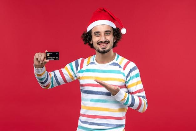 Jovem do sexo masculino segurando um cartão de banco preto na parede vermelha feriado