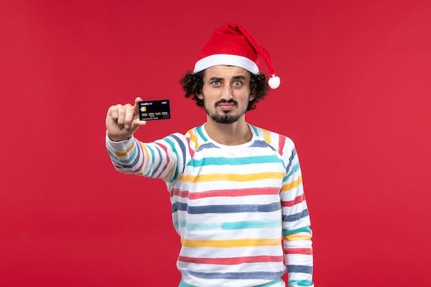 Jovem do sexo masculino segurando um cartão preto do banco em uma parede vermelha no feriado de ano novo com dinheiro vermelho