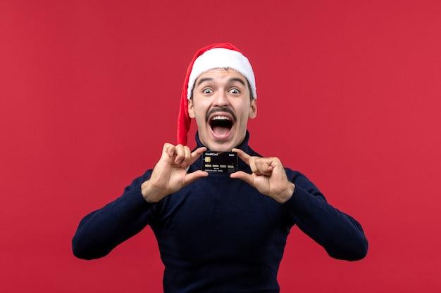 Jovem do sexo masculino segurando um cartão preto sobre o fundo vermelho