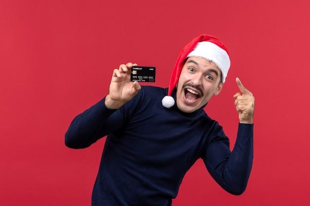 Jovem do sexo masculino segurando um cartão preto sobre o fundo vermelho Foto gratuita