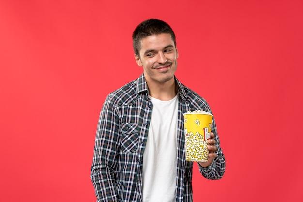 Jovem do sexo masculino segurando um pacote de pipoca e sorrindo levemente em frente ao filme de cinema de parede vermelho-claro
